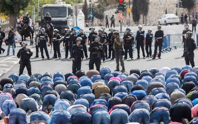 Les Palestiniens prient tandis que des policiers israéliens regardent dans le quartier de Wadi al-Joz, le 9 octobre 2015 à Jérusalem-Est. La police israélienne a imposé une limite d'âge vendredi aux Palestiniens qui veulent entrer dans la Vieille Ville, autorisant seulement les hommes âgés de plus de 45 et toutes les femmes à entrer (Crédit : Yonatan Sindel / Flash90)
