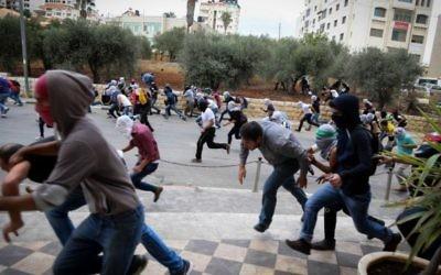 Des émeutiers palestiniens lançant des pierres pendant des affrontement avec les troupes israéliennes à Bet El, près de la ville cisjordanienne de Ramallah, le 10 octobre 2015 (Flash90)
