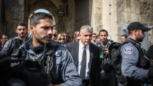 Le chef du parti Yesh Atid, Yaïr Lapid, entouré par des policiers lors d'une visite à la Porte des Lions, dans la Vieille Ville de Jérusalem sur le site d'une tentative d'attaque au couteau le 12 octobre 2015 (Crédit : Hadas Parush / Flash90)