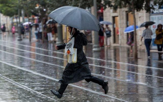 Un homme ultra-orthodoxe tient un parapluie dans la rue de Jaffa, dans le centre de Jérusalem pour un jour de pluie, le 25 octobre 2015 (Crédit : Yonatan Sindel / Flash90)