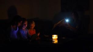 Une famille israélienne assise dans l'obscurité dans leur maison pendant une panne de courant, près de la ville israélienne de Netanya, le 26 octobre 2015 (Crédit : Chen Leopold / FLASH90)