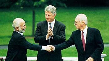 Une poignée de main entre Hussein I de Jordanie et Yitzhak Rabin, accompagné de Bill Clinton, pendant les négociations de paix israélo-jordaniennes (Crédit : Maison Blanche, domaine public)