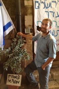 L'organisateur Yair Dan se trouve à côté d'un jeune arbre à la tente de protestation, le 8 octobre, 2015 (Crédit : Elhanan Miller / Times of Israël)