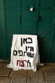 """Une pancarte sur laquelle on peut lire """"Ici étaient les complices de l'assassinat"""", est posée contre la porte d'un magasin fermé situé sur la rue palestinienne Hagai, le 8 octobre, 2015 (Crédit : Elhanan Miller / Times of Israël)"""