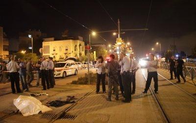 Des policiers israéliens se tenant près du corps de Fadi Aloon, un Palestinien qui aurait poignardé un garçon de 15 ans près  de la Vieille Ville de Jérusalem, avant d'être abattu et tué par la police tôt dimanche matin, le 4 octobre 2015 (Crédit photo: Flash90)
