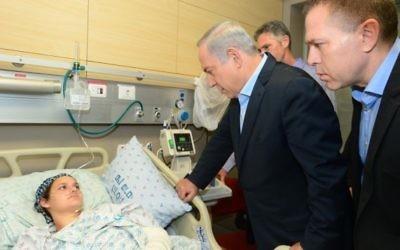 Le Premier ministre Benjamin Netanyahu et le ministre de la Sécurité intérieure rendent visite à Adèle Benet et à son bébé, qui ont été blessés  le 3 octobre 2015 dans un attentat terroriste dans la Vieille Ville de Jérusalem au cours duquel Aharon Benet a été assassiné, à l'hôpital Hadassah Ein Kerem à Jérusalem, le 5 octobre 2015 (Crédit : Kobi Gideon / GPO)