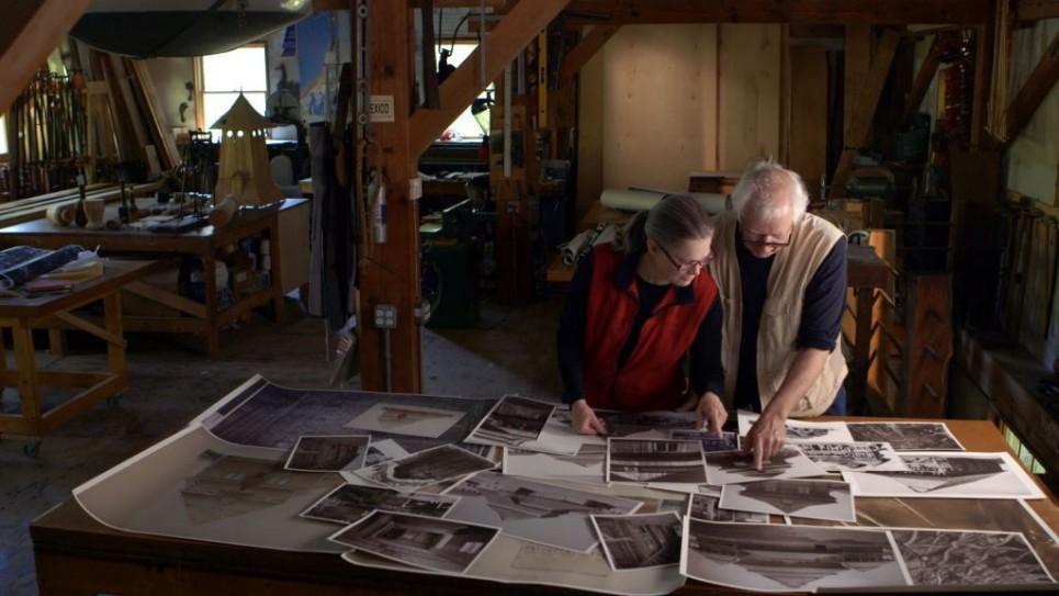 Les artistes Rick et Laura Brown examinant les photos des synagogues polonaises qui n'existent plus pour aider à la reconstruction de la synagogue Gwoździec (Crédit : Trillium Studios production)