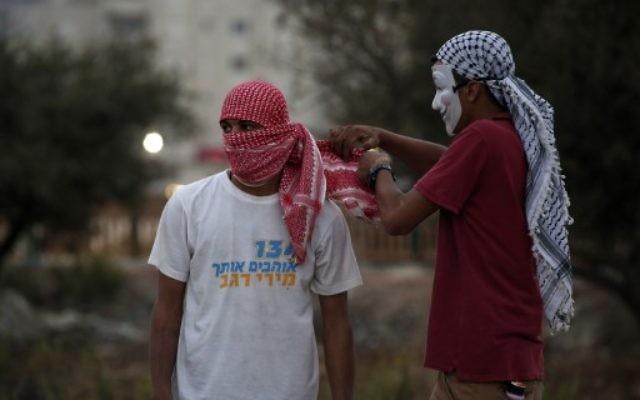 Un jeune Palestinien portant un ancien t-shirt de la campagne pour les primaires du Likud de la ministre de la Culture Miri Regev lors d'affrontements avec l'armée israélienne dans la ville de Ramallah en Cisjordanie, le 4 ioctobre 2015 (Crédit photo: Abbas Momani / AFP)