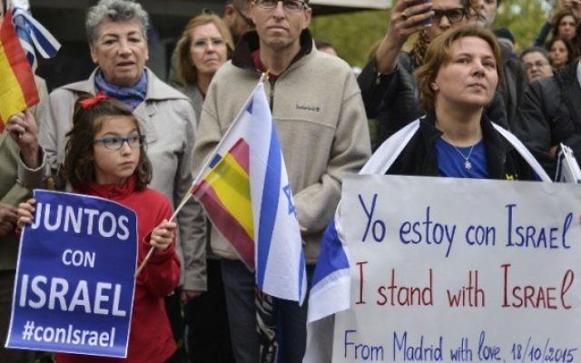 """Drapeaux israéliens et espagnols ainsi que des pancartes """"Ensemble avec Israël"""" pendant un rassemblement organisé par la Fédération des communautés juives d'Espagne (FCJE) et la communauté juive de Madrid devant l'ambassade d'Israël à Madrid, le 18 octobre 2015 (Crédit : PEDRO ARMESTRE / AFP)"""