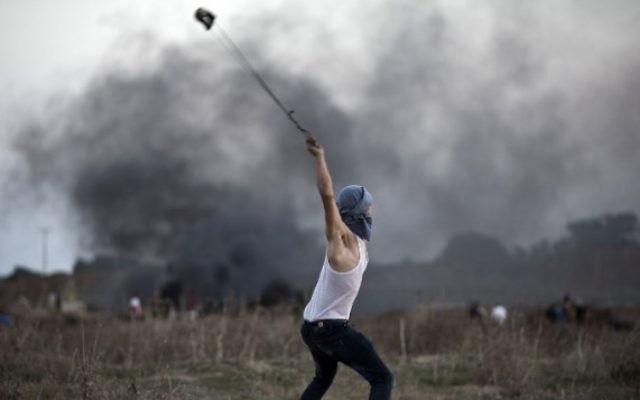 Un émeutier palestinien utilise un lance-pierre pour jeter des pierres sur des soldats israéliens lors d'affrontements, près de la barrière de sécurité entre Israël et la bande de Gaza, le 15 octobre 2015. Illustration. (Crédit : Mohammed Abed/AFP)