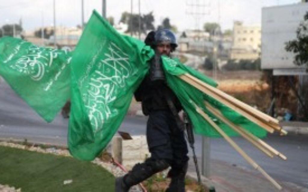 Un membre des forces de sécurité israéliennes porte  des drapeaux de l'organisation terroriste du Hamas qui ont été saisis lors d'affrontements avec des manifestants palestiniens près de limplantation de Beit El en Cisjordanie, le 8 octobre 2015 (Credit photo: Abbas Momani / AFP)