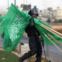 Un membre des forces de sécurité israéliennes porte  des drapeaux de l'organisation terroriste du Hamas qui ont été saisis lors d'affrontements avec des manifestants palestiniens près de limplantation de Beit El en Cisjordanie, le 8 octobre 2015 (Credit photo: Abbas Momani / AFP)