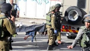 Des soldats de Tsahal portent le corps d'un Palestinien qui a poignardé et blessé un soldat avant d'être abattu par un agent de la police des frontières à Hébron le 29 octobre 2015 (Crédit photo: Hazem Bader / AFP)