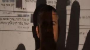 Le député de HaBayit HaYehudi, Yinon Magal, couvert par l'ombre d'une main dans un clip posté par plusieurs députés visant à mettre en évidence les dangers de l'incitation en ligne. (Crédit : Capture d'écran Deuxième chaîne)