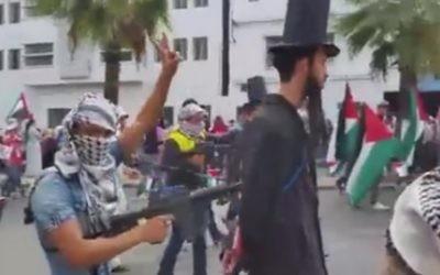 """Manifestation pro-palestinienne à Casablanca, au Maroc, dans laquelle """"des Juifs"""" sont tenus à la pointe d'une mitraillette par des manifestants vêtus de keffiehs, le 25 octobre 2015 (Capture d'écran: alyaexpress-news.com)"""