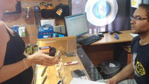 Une femme achetant un spray au poivre à Tel-Aviv (Crédit : Simona Weinglass / Times of Israël)