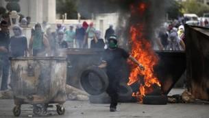 Photo illustrative d'un manifestant palestinien brûlant des pneus lors d'affrontements avec les forces de sécurité israéliennes en Cisjordanie le 10 octobre 2015 (Crédit photo: Abbas Momani / AFP)