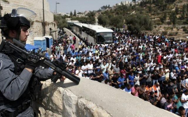 Un policier monte la garde alors que des Palestiniens, qui ont été empêchés de pénétrer dans l'enceinte du mont du Temple en raison de restrictions d'âge sur des hommes musulmans pour participer à la prière du vendredi, prient à la Porte des Lions dans la Vieille Ville de Jérusalem, le 2 octobre 2015 (Crédit photo: Thomas Coex / AFP)