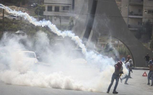 Des manifestants palestiniens courent pour échapper à des gaz lacrymogènes lors d'affrontement avec la police après une manifestation dans la ville de Ramallah en Cisjordanie, le 5 octobre 2015 (Crédit photo: Flash90)