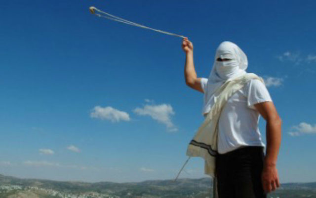 Un habitant d'une implantation de Cisjordanie, lançant des pierres (Crédit photo: Mendy Hechtman / Flash90)