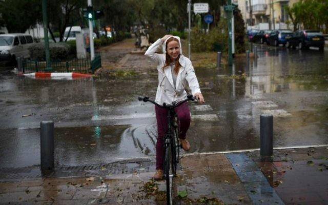 La députée Stav Shaffir (Union sioniste) circule à vélo à travers une forte pluie et des vents forts alors qu'un un orage frappe Tel Aviv, le 25 octobre 2015 (Crédit photo: Ben Kelmer / Flash90)
