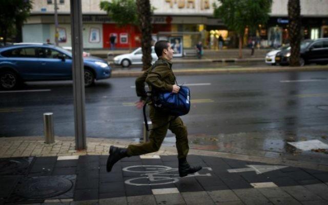 Un soldat israélien court sous une forte pluie et des vents forts alors qu'un un orage frappe Tel Aviv, le 25 octobre 2015 (Crédit photo: Ben Kelmer / Flash90)