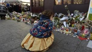 Une enfant visite un site commémoratif le 15 novembre à 2015 à l'extérieur du restaurant Petit Cambodge, dans le 10ème arrondissement de Paris, pour les victimes des attaques terroristes du 13 novembre à Paris. (Crédit : AFP)