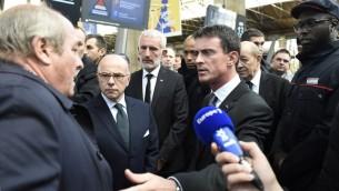 Un homme (g), qui est à la recherche de sa fille, qui avait été au Bataclan dans la nuit des attaques de Paris le 13 novembre, parle avec le Premier ministre français Manuel Valls (3e D), le ministre de la Défense français Jean-Yves Le Drian (2e D), le président de la SNCF Guillaume Pepy (C) et le ministre de l'Intérieur français Bernard Cazeneuve (2e g) à la gare du Nord à Paris, le 15 Novembre 2015. (Crédit : AFP PHOTO / ERIC FEFERBERG)
