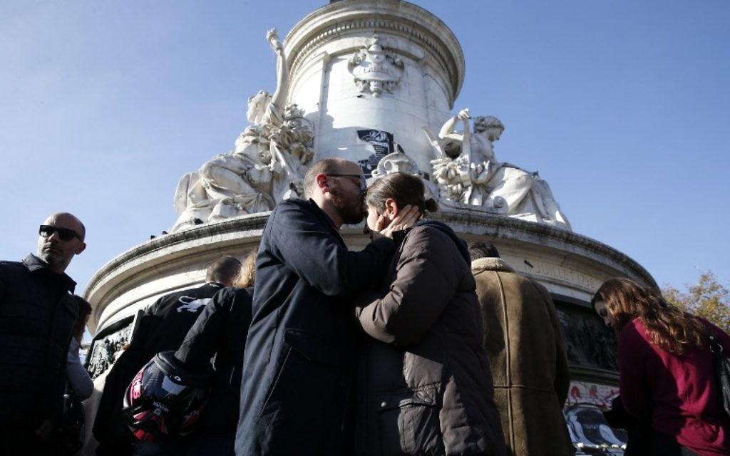 Des gens se réconfortent sur la place de la République le 15 novembre 2015 (crédit : AFP)