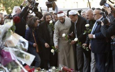 L'auteur français Marek Halter (4e à gauche), l'imam de la mosquée de Drancy, Hassen Chalghoumi (6e à gauche), les représentants des communautés juives et musulmanes et autres se réunissent à un mémorial de fortune près de la salle de concert au Bataclan à Paris le 15 novembre, 2015, deux jours après une série d'attaques meurtrières. (Crédit : AFP / Miguel Medina)