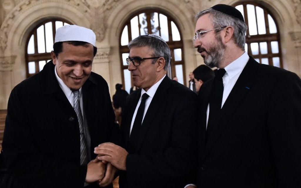 Le rabbin Moshe Sebbag (d) et l'imam de la mosquée de Drancy, Hassan Chalghoumi (g) arrivent à la Grande synagogue de la Victoire avant de rendre hommage aux victimes d'une série d'attaques meurtrières, le 15 novembre 2015. (Crédit : AFP PHOTO / LOIC VENANCE)