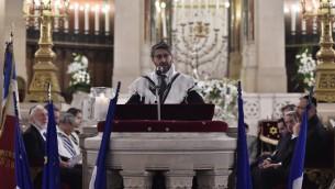 Le Grand Rabbin de France Haïm Korsia prie en hommage aux victimes d'une série d'attaques meurtrières à la Grande synagogue de la Victoire, le 15 novembre 2015. (Crédit : AFP PHOTO / LOIC VENANCE)