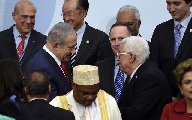 Le Premier ministre Benjamin Netanyahu  (à gauche) avec le président de l'Autorité palestinienne Mahmoud Abbas lors de la photo de famille de la COP21, la conférence des Nations unies sur le changement climatique, au Bourget , le 30 novembre 2015 (Crédit : Martin Bureau/Pool/AFP)