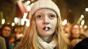 Une fille avec les lèvres peintes en drapeau tricolore français assiste à une veillée à la mémoire des victimes de Paris en face de l'ambassade française le 15 novembre 2015 à Copenhague. (Crédit : AFP PHOTO / Nils Meilvang / SCANPIX DANEMARK / NILS MEILVANG +++ DANEMARK OUT)