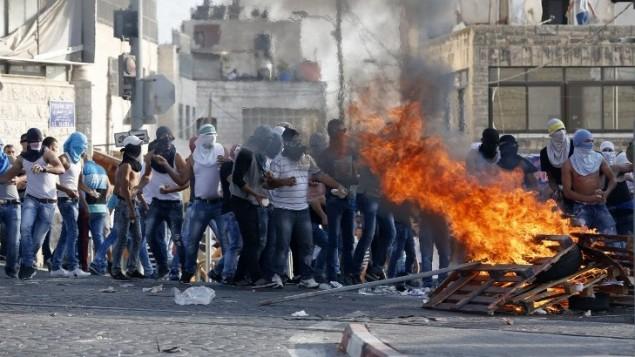 Des lanceurs de pierres palestiniens près d'un feu de bois lors d'affrontements avec les forces de sécurité israéliennes à Shuafat, à Jérusalem Est, le 5 octobre 2015 (Crédit : AFP/Ahmad Gharabli)