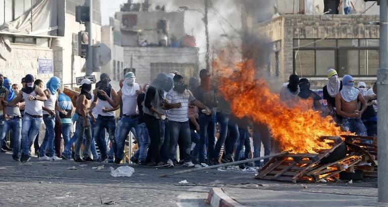 Des lanceurs de pierres palestiniens près d'un feu de du bois lors d'affrontements avec les forces de sécurité israéliennes à Shuafat à Jérusalem-Est le 5 octobre 2015 (Crédit : AFP Photo / Ahmad Gharabli)