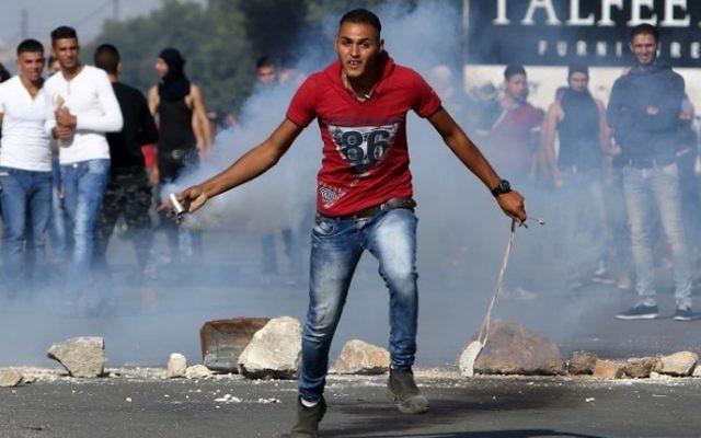Un manifestant palestinien jette une cartouche de gaz lacrymogène lors d'affrontements avec les soldats israéliens au checkpoint de Hawara, au sud de la ville de Naplouse en Cisjordanie, le 9 octobre 2015 (Crédit photo: JAAFAR ASHTIYEH / AFP)
