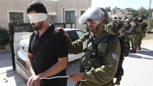 Les forces de sécurité israélienne arrêtant et bandant les yeux d'un Palestinien lors d'affrontements dans le village de Beit Omar, près de Hébron, en Cisjordanie le 11 octobre 2015 (Crédit : AFP / Hazem Bader)