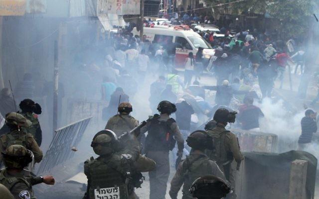 Les forces de sécurité utilise du gaz lacrymogène pour disperser des manifestants palestiniens lors d'une manifestation dans la ville de Hébron en Cisjordanie, le 27 octobre 2015 (Crédit : AFP Photo / Hazem Bader)
