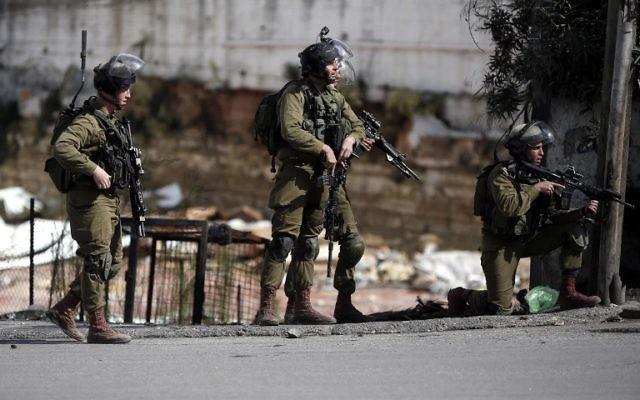 Les forces de sécurité israéliennes se tiennent dans une rue lors d'affrontements avec des manifestants palestiniens dans la ville cisjordanienne de Hébron, le 30 octobre 2015  (Crédit : AFP / Thomas Coex)