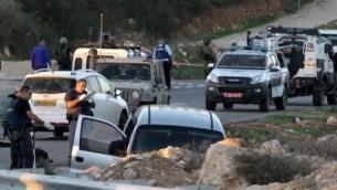 Des soldats et des policiers israéliens inspectent une voiture après une attaque meurtrière près de l'implantation d'Otniel, au sud de la ville d'Hébron en Cisjordanie le 13 novembre 2015 (Crédit : AFP PHOTO / HAZEM BADER)