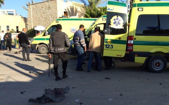 Les secouristes et les forces de sécurité se tiennent à côté d'une ambulances en dehors de l'hôtel Swiss Inn dans la ville égyptienne d'El-Arish, dans la péninsule du Sinaï, à la suite d'une attaque contre l'hôtel menée par deux kamikazes et un homme armé le 24 novembre 2015 (Crédit : AFP PHOTO / STR / AFP)