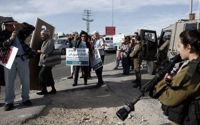 Les militant pour la paix israéliens et palestiniens passant devant les troupes de l'armée  lors d'une manifestation en Cisjordanie le 27 novembre 2015 (Crédit : AFP PHOTO / THOMAS COEX)