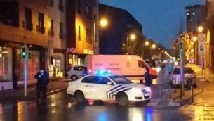 Une photo prise avec un  téléphone portable le 14 novembre 2015 montre une camionnette de l'unité belge de déminage SEDEE tandis que les policiers bloquent une rue lors d'un raid de la police dans le quartier de Molenbeek à Bruxelles, peut-être en relation avec les attentats meurtriers du 13 novembre à Paris (Crédit : AFP Photo / Belga / Hendrik Devriendt)