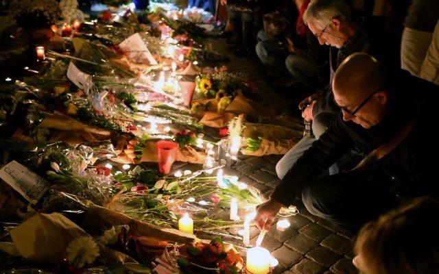 Les gens allument des bougies et déposent des fleurs, le 14 novembre, 2015 au mémorial de fortune devant l'ambassade française à Rome après une série d'attaques coordonnées dans et autour de Paris le 13 novembre (Crédit : AFP PHOTO / VINCENZO PINTO)
