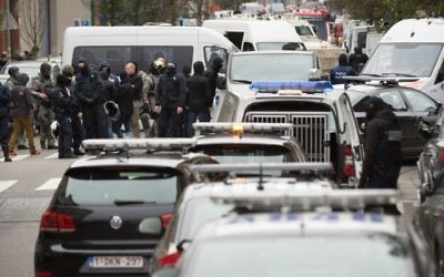 Les forces de sécurité du personnel pendant une opération dans le quartier de Molenbeek à Bruxelles le 16 novembre 2015. La police belge a lancé une nouvelle opération majeure dans le quartier de Molenbeek à Bruxelles, où plusieurs suspects dans les attentats de Paris avaient déjà vécu, le 16 novembre (Crédit ; AFP PHOTO / BELGA PHOTO immédiate / BENOIT DOPPAGNE)