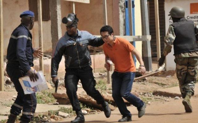 Illustration :Les forces de sécurité maliennes évacuent un homme d'une zone autour de l'hôtel Radisson Blu à Bamako le 20 novembre 2015. (Crédit : AFP PHOTO / HABIBOU KOUYATE)