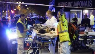 Les secouristes évacuent un blessé près de la salle de concert Le Bataclan à Paris, le 14 novembre 2015 (Crédit : AFP PHOTO / MIGUEL MEDINA)
