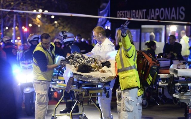 Les secouristes évacuent un blessé près de la salle de concert Le Bataclan à Paris, le 14 novembre 2015 (Crédit : Miguel Medina/AFP)