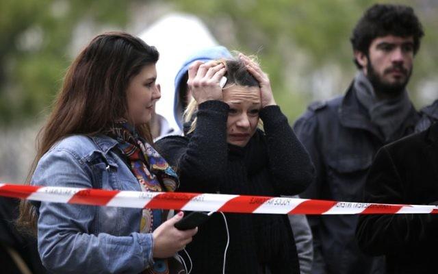 Une femme pleure devant le Bataclan après les attentats de Paris du 13 novembre 2015  (Crédit : AFP)